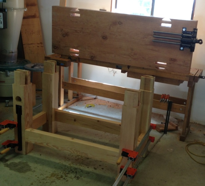 Manhandling the bench top, first I set it on edge, then down half way onto the legs, then walked it into place