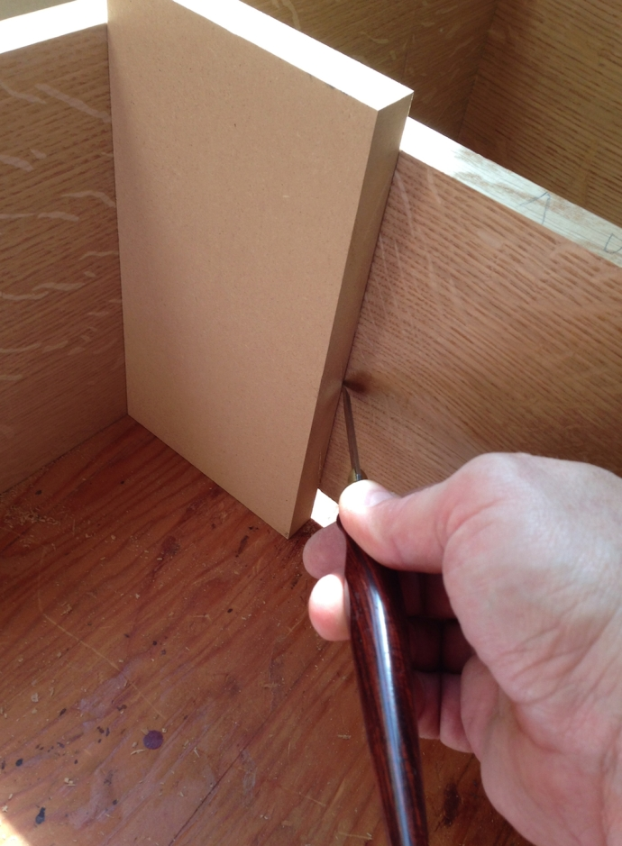 Using a spacer block to lay out the shelf dado