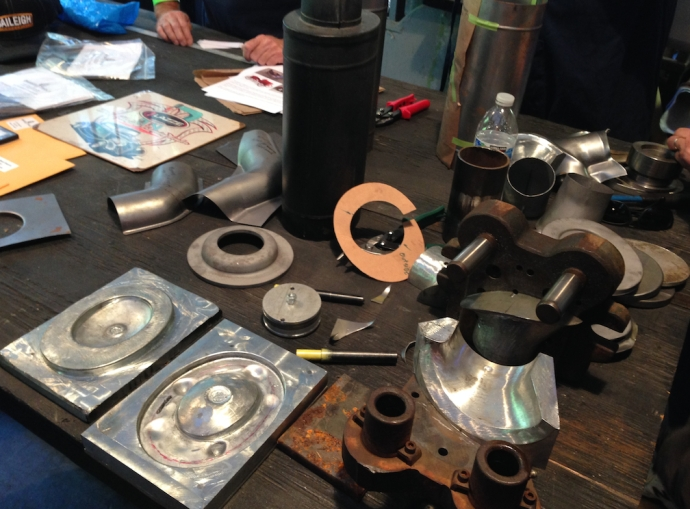 Various parts and dies for producing the replica air cleaners.  The silver dies are cast in Kirksite using a sand mold produced directly from the original part -- which is the black unit in the center of the photo