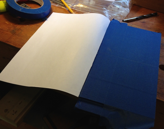 Lay down blue tape to prevent the spray adhesive from gumming up the wood.  Strike a center line on the part.