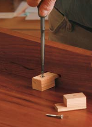 Wooden buttons for attaching a table top (see https://www.finewoodworking.com/media/TabletopsFlat.pdf, click picture to read article)