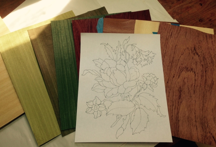 Here is the design, and the veneers I'm using.  Light, medium and dark green for the foliage and stems, bloodwood, bubinga and satinwood for the flowers.