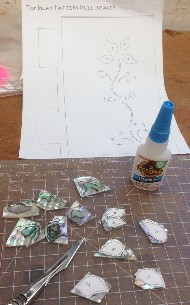 The pattern is cut into individual parts and glued to the abalone blanks with super glue.  I had one extra piece of shell when it was all said and done.