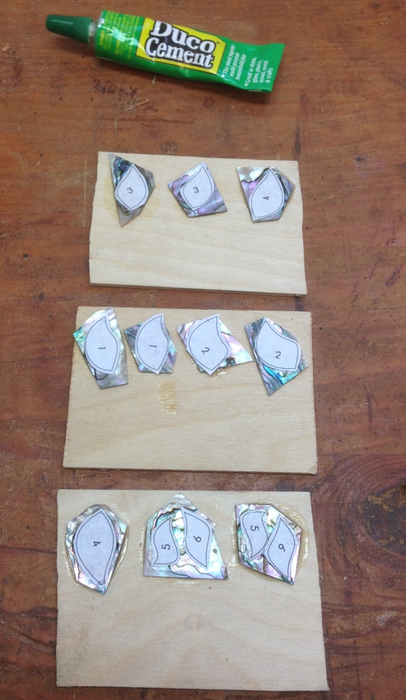 """The shell blanks are Duco'd to 1/8"""" plywood scraps.  The plywood gives me something to hang on to while sawing, and helps support the delicate shell.  I used the marquetry chevalet for sawing, you could use a jeweler's saw or maybe a scroll saw too."""