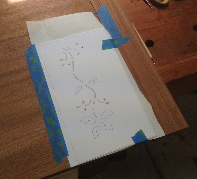 """The pattern is oriented on the top, with a piece of transfer paper under it.  I trace the entire design.  The tracing of the vines is used directly to route that part of the design.  I mark the location of the """"bugs"""" with an awl and then drill those."""